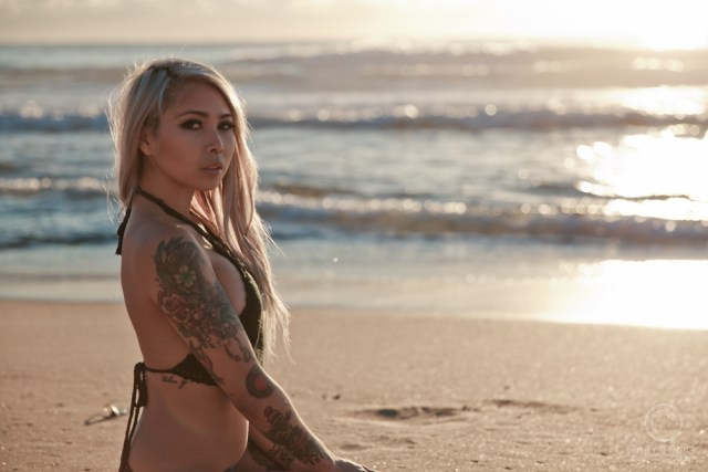 asian girl with tattoos sitting in the sand