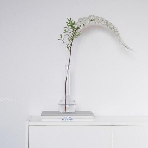 Sideboard dekorieren mit Spiere Blüte weiß in Glasvase als Frühlingsdeko, wohnen einrichten skandinavisch modern minimalistisch schlicht monochrom reduziert Wohninspiration Wohnideen Wohnblog Tasteboykott Interieur Interior Design Deko