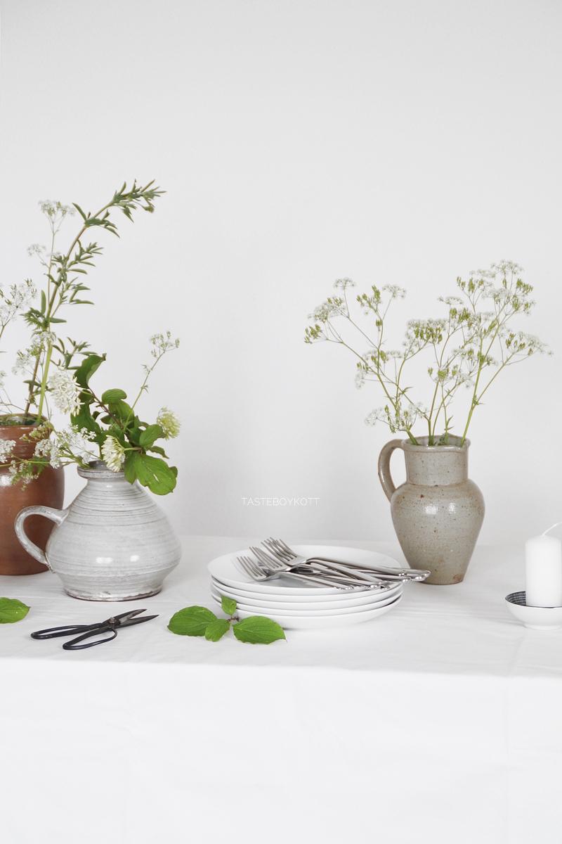 Rustikal-schlichte Tischdeko für Mittsommer. Tisch dekorieren mit Wiesenblumen, Tonkrügen, weißer Tischdecke und Kerzen. Dekoideen Wohninspiration Tasteboykott Wohnblog.