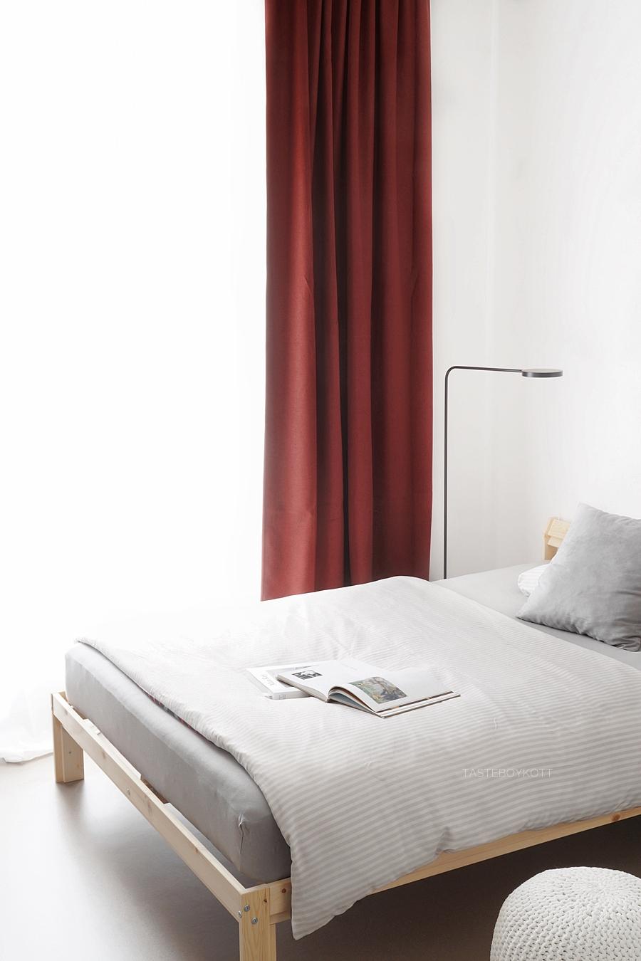 Schlafzimmer modern skandinavisch schlicht grau weiß mit Holzbett von Ikea, schwarzer Stehleuchte, Vorhang und Kissen. Wohnheimzimmer einrichten Tipps und Wohnideen Tasteboykott.
