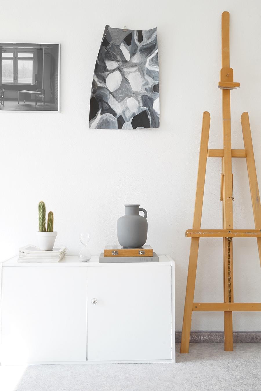Schlafzimmer/ Jugendzimmer skandinavisch modern minimalistisch einrichten mit dem Farbkonzept grau, weiß, Holz. Sideboard dekorieren mit Vase, Kaktus, Büchern und Staffelei. Monochrome schlichte Herbstdeko in Grautönen Inspiration. Wohnblog Tasteboykott Wohninspiration Dekoideen Interior Design Blog.