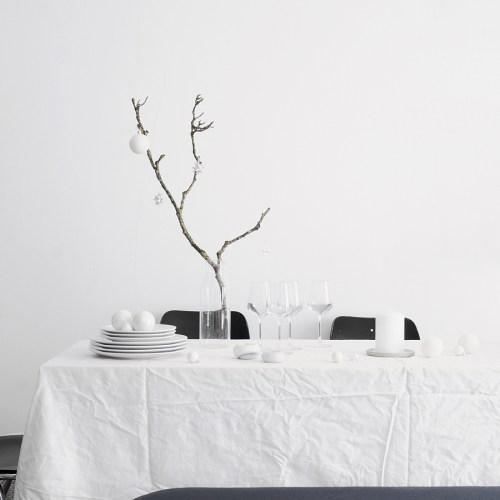 Minimalistische Tischdeko für Weihnachten, ganz in weiß: Esstisch modern dekorieren mit Kugeln, Zweigen, Kerzen und Teelichtern