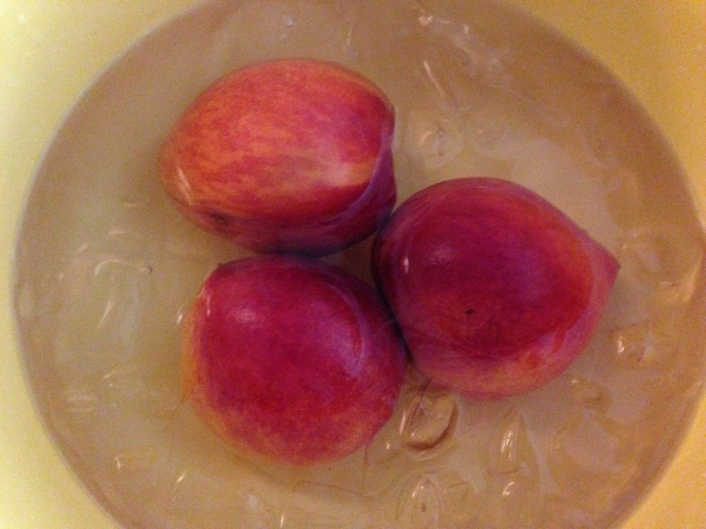 Place peaches in an ice bath so that the skins slide off easily