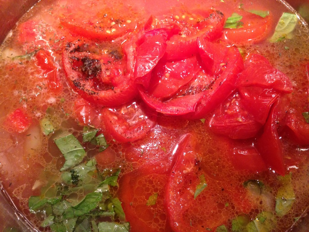Tomatoes, onions, basil, and chicken broth simmering in a large saucepan