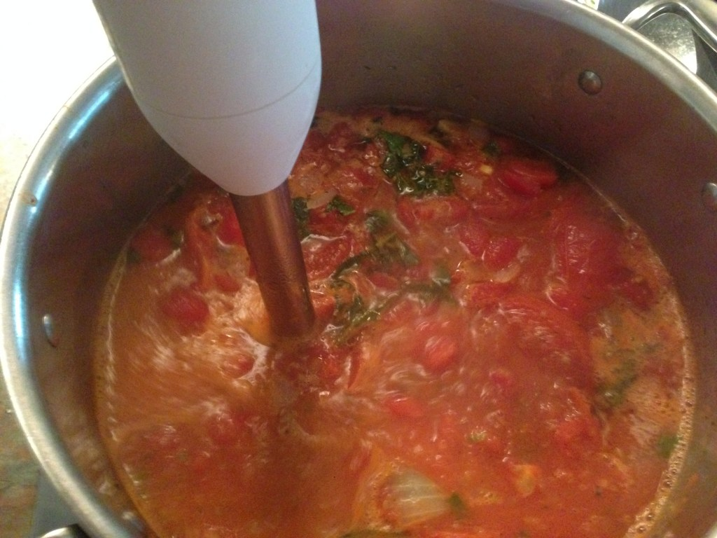 Ingredients for Roasted Tomato Basil soup being combined with an immersion blender