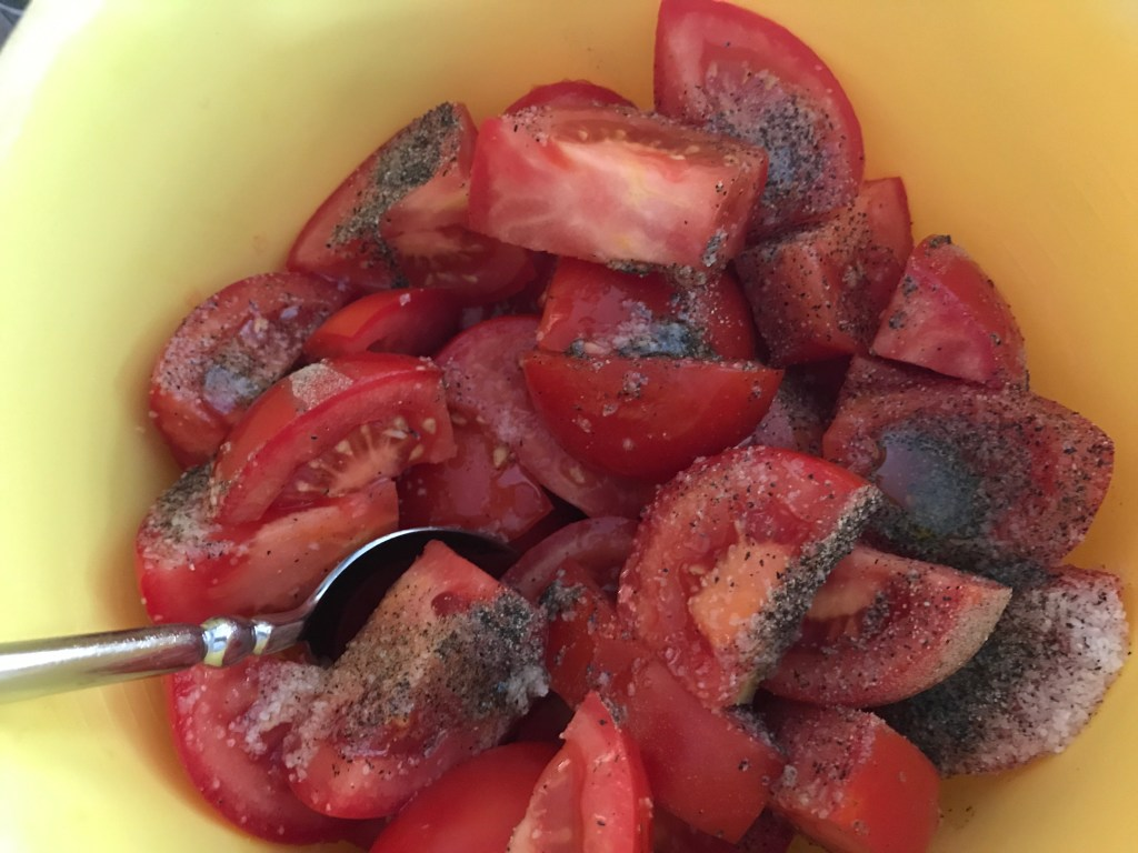 Fresh tomatoes in a bowl with salt, pepper, and olive oil