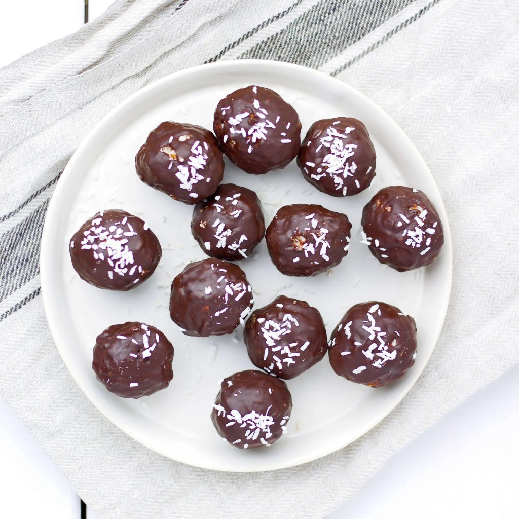 Vegan coconut and almond truffles covered with dark chocolate.