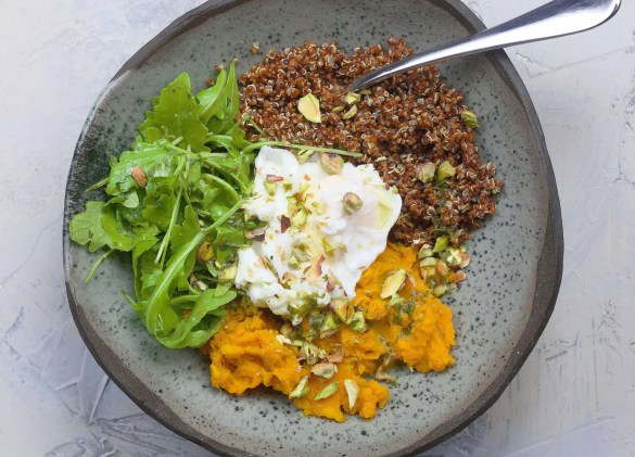 1 cup red quinoa 2 large sweet potatoes, cut into chunks 3 tbsp olive oil 1-2 teaspoons turmeric 3 cloves garlic 2 cups vegetable bullion 1/4 cup lemon juice 2 teaspoons agave syrup 1/4 cup parsley leaves salt freshly cracked black pepper 2 poached eggs handful fresh rucola crushed pistachios or other nuts for topping