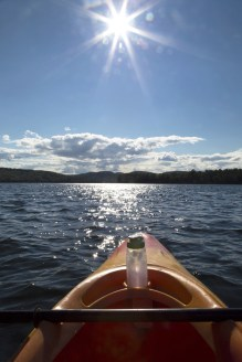 Front of kayak pointed out into the open water of Squam Lake, New Hampshire. Sunburst and blue sky overhead. Water bottle visible.