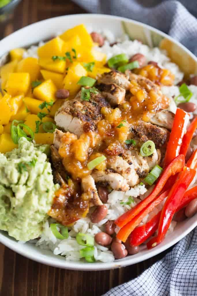 Bowl of Caribbean jerk chicken, mangos, mashed avocado and bell peppers over rice. | tastesbetterfromscratch.com