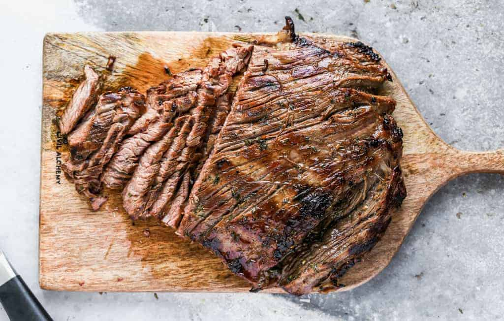 Marinated flank steak being cut into thin slices on a cutting board..