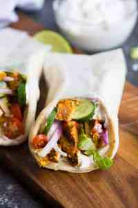 Chicken Gyros include delicious marinated chicken, grilled, and layered on a pita with lettuce, tomato, onion and cucumber. This fresh and healthy meal idea is one of our family favorites! | tastesbetterfromscratch.com