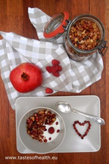 An image of Homemade Granola with Red Berries (strawberries, raspberries) in a jar and also served in a bowl with yogurt and pomegranate seeds.