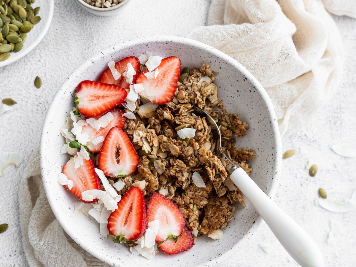 bowl of coconut granola with strawberries in it