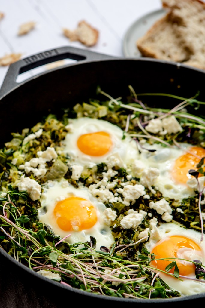 pesto eggs in a skillet with zucchini and kale
