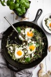 skillet with green shakshuka in it with one egg scooped out