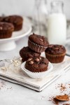 double chocolate zucchini muffin on a tray with muffins stacked behind it