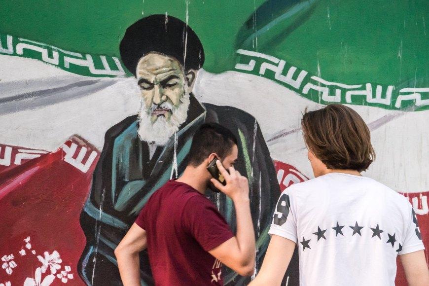 Unge foran vægmaleri af Khomeni