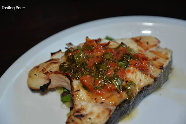 Grilled Halibut Steaks Topped with sun dried tomatoes, onions, basil