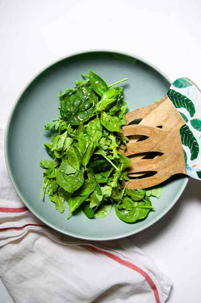 Arugula Salad in a blue bowl with white napkin