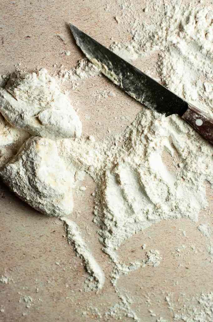 dough and a knife on floured surface