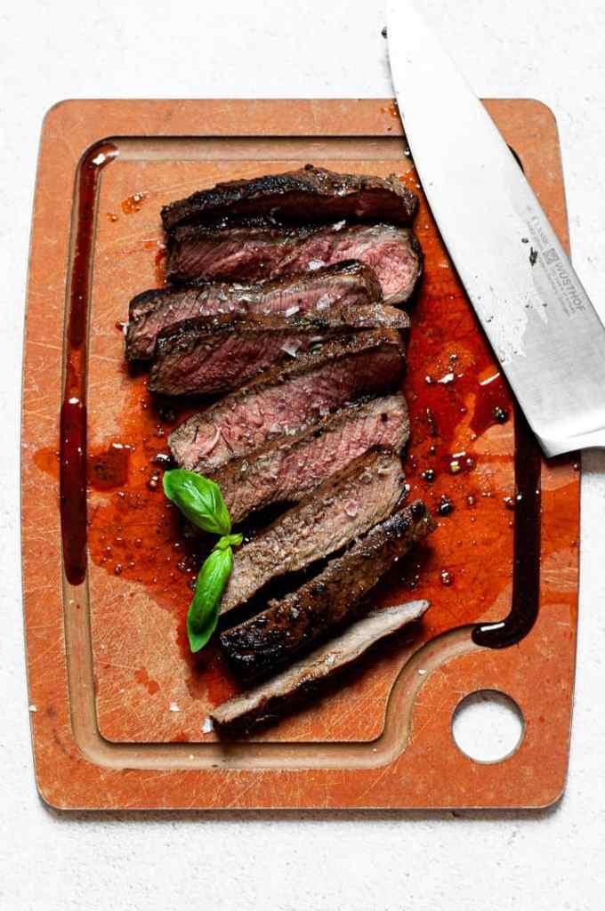 Freshly cut skirt steak on a cutting board with a knife