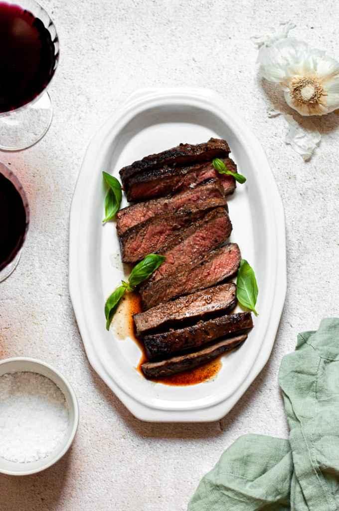 Skirt steak on a platter with basil
