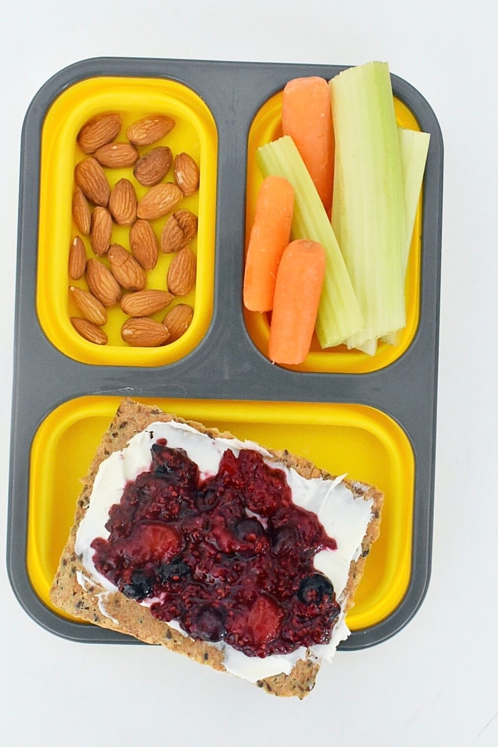 yellow bento box with almonds, carrots, celery sticks and mixed berry chia jam and mascarpone cheese on crispbread