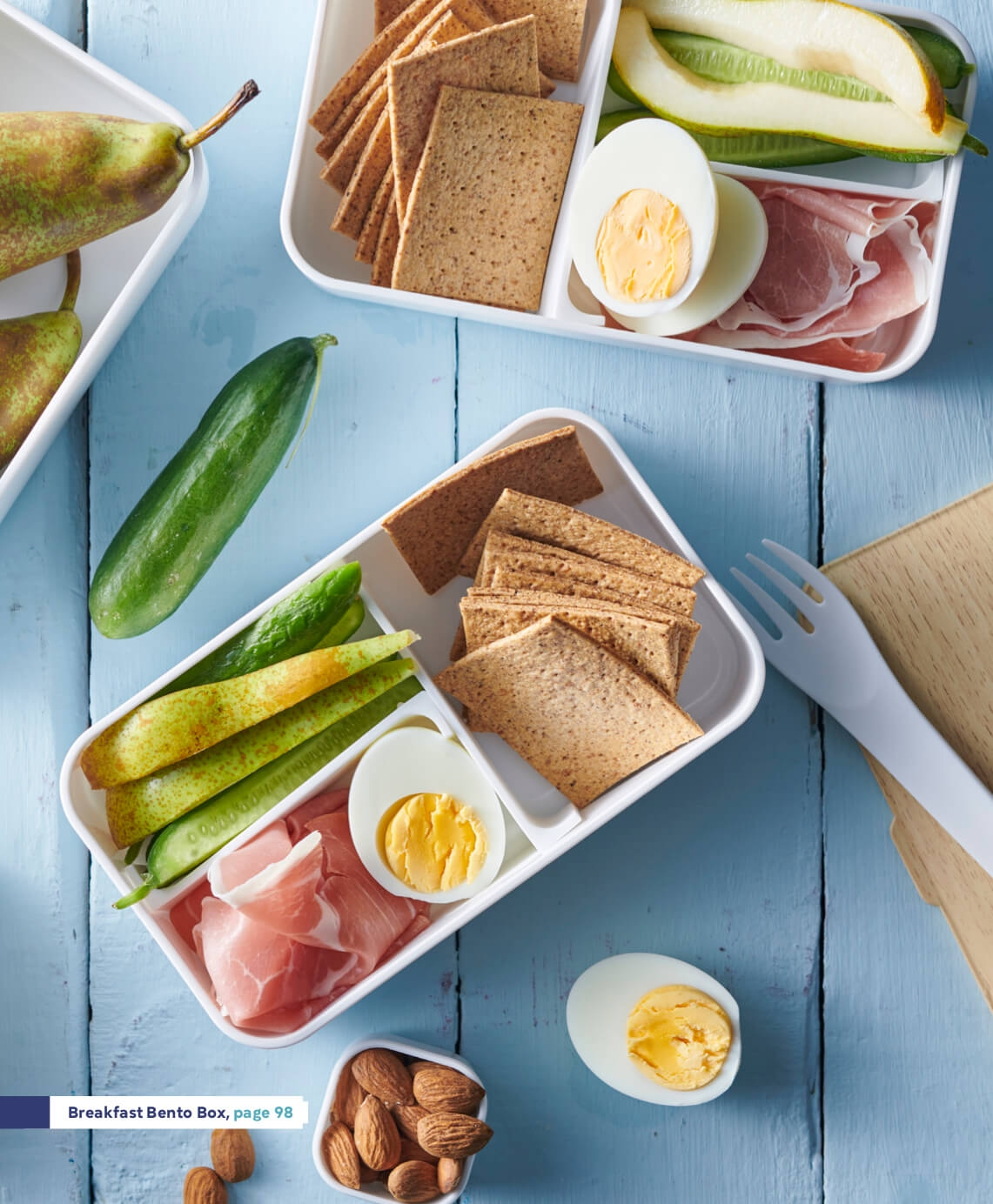 white wood background with breakfast bento box containing sliced Persian cucumber, sliced pear, crispbread, hard boiled eggs, prosciutto slices and unsalted almonds