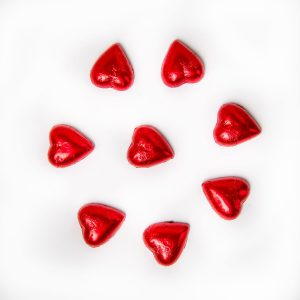 8 red foil wrapped milk chocolate hearts.