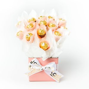 14 Ferreo Rocher chocolates surrounded by white cello, in a baby pink box.