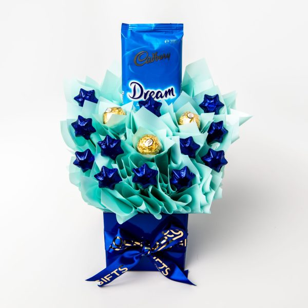 A whole 200gm slab of Dream white chocolate with 12 blue star shaped milk chocolates and 3 Ferrero Rocher chocolates all surrounded by baby blue cello in a small blue box.