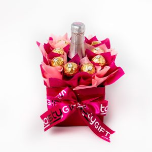 """A Yellowglen pink piccolo surrounded by 10 Ferrero Rocher chocolates """"leafed"""" in pink and baby pink cello in a small pink box. Finished with a pink ribbon with gold print."""
