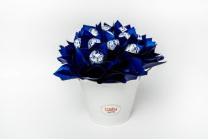 """13 Baci chocolates wrapped in clear cello and """"leafed"""" in royal blue cello surrounded by royal blue cello in a small white keepsake metal bucket."""