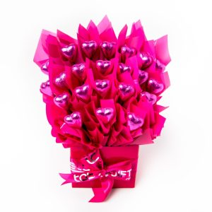 22 pink foil wrapped milk chocolate hearts surrounded by pink cello in a small pink box.