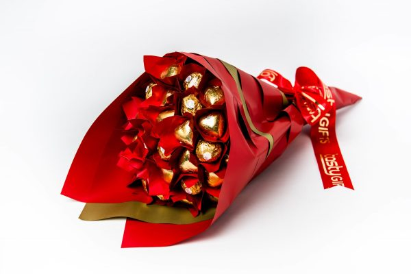 10 Ferrero Rocher chocolates and 17 gold foil wrapped milk chocolate hearts wrapped in clear and leafed in red cello. All wrapped up in red and gold cello.