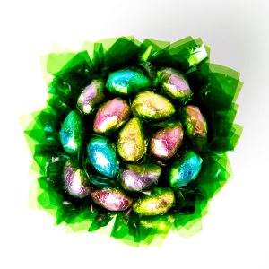 """15 Milk chocolate half eggs wrapped in clear and """"leafed"""" in green, surrounded by green cello in a small white polka dot box."""