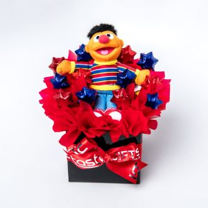 A 16cm Sesame Street Ernie beanie and 12 red and blue foil wrapped milk chocolate hearts surrounded by red cello in a small black box.