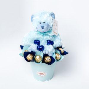 A 20cm Blue Teddy Bear, 12 Ferrero Rocher chocolates and 3 blue foil wrapped milk chocolate hearts in a small baby blue keepsake metal bucket.