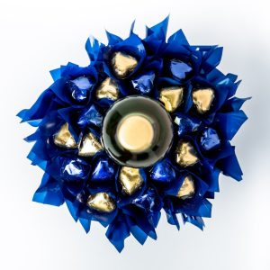A 750ml bottle of Jarvis Estate white wine with 20 blue and gold foil wrapped milk chocolate hearts, surrounded by blue cello in a small blue box. Finished with a blue ribbon with gold print.