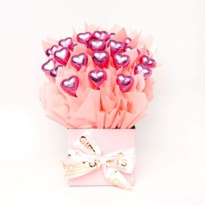 22 pink foil wrapped milk chocolate hearts surrounded by baby pink cello in a small baby pink box.