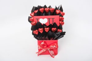 """A 100g Bloomsberry """"I ♥ U"""" dark chocolate bar and 16 red foil wrapped milk chocolate hearts surrounded by black cello in a small red box. Finished with a red ribbon with silver print."""