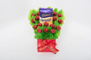 A 180g Cadbury Caramilk bar and 16 red foil wrapped milk chocolate stars surrounded by lime green cello in a small red box. Finished with a red ribbon with gold print.
