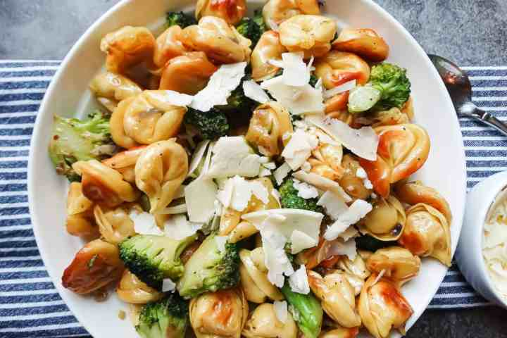 pan fried tortellini and broccoli in a white serving dish