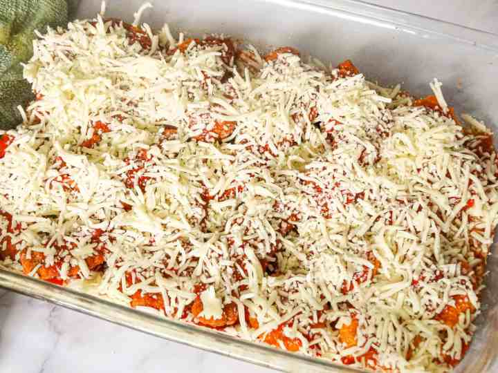 chicken tenders parmigiana uncooked in a glass baking dish