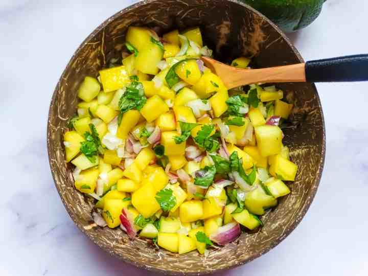 easy mango salsa in a coconut bowl with a spoon