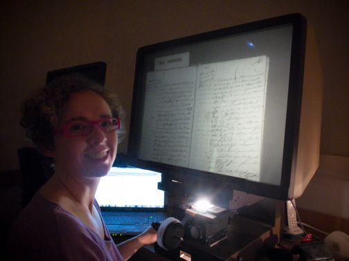 Mireia Nieto, genealogista profesional, consultando documento microfilmado