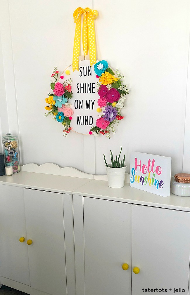 How to make a felt flower hoop saying wreath. Create a saying for spring and put it inside an embroidery wreath with felt flowers. It's fun to make and will welcome visitors to your home all summer long!