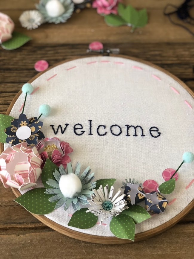 Make an embroidery hoop wall hanging. A hand-stitched word is surrounded by vibrant paper flowers in an embroidery hoop. Make one for your home or to give as a gift!