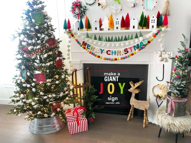 Make a GIANT JOY sign for under $10. An unfinished board, trim, embroidery hoop, yarn, letters and spray paint combine to create something special for the holidays!